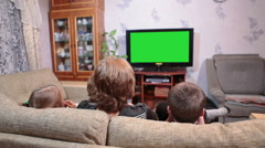 Mother with two children watching tv show on green screen in living room Stock Footage