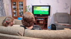Mature mother with young daughter watching cartoons on tv in living room - stock footage