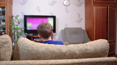 Preschool boy watching cartoons an tv set while sitting on sofa in living room Stock Footage