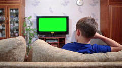 Young boy sitting on sofa and watching green screen tv in living room Stock Footage