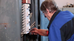 Mature electrician working with screwdriver in rubber glove in high voltage box - stock footage
