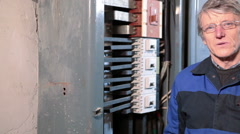 Mature electrician worker speaking and looking at camera, camera moving right - stock footage