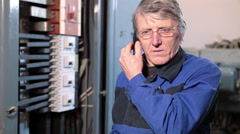 Mature electrician worker in glasses talking with cellphone in high voltage room - stock footage