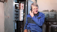 Senior electrician worker in glasses talking with cellphone in high voltage room - stock footage