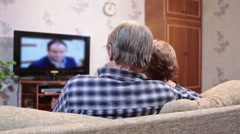 Mature couple watching tv set sitting together on sofa in living room Stock Footage