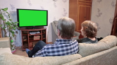 Senior couple watching tv with green screen, sitting sofa and talking Stock Footage