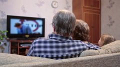 Mature mother and father with daughter watching soap opera on tv in living room Stock Footage