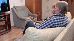 Side view of talking senior couple sitting on sofa and watching lcd tv - stock footage
