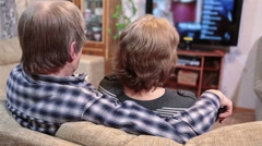 Senior couple sitting sofa and wachin LCD TV embracing together, rear view Stock Footage
