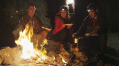 Eating over campfire Stock Footage