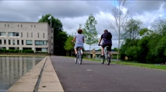 Two people ride bicycles on a path by water Stock Footage