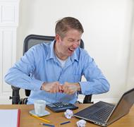 mature man in rage while working - stock photo
