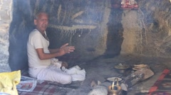 Indian sadhu, holy man preparing chapatti on fire in holy cave. Devprayag, India Stock Footage