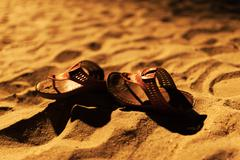 Stock Photo of bride shoes on sand night time .