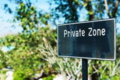 Private zone sign standing for restricted access Stock Photos
