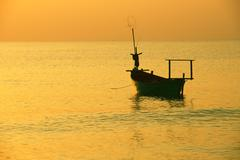 Fishing boat at sunset tropical sea Stock Photos