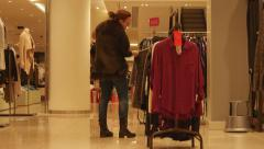 Woman chosing clothes in store Stock Footage