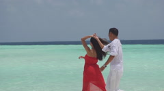 Multicultural Couple In Love Dances Playfully Along Maldivian Seaside Stock Footage