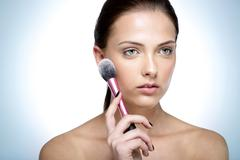 portrait of a young beautful woman holding cosmetic brush - stock photo
