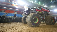 The giant offroader with huge wheels rides on the sandy arena Stock Footage