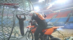 Biker drives into metal mesh ball on the entertainment show Stock Footage
