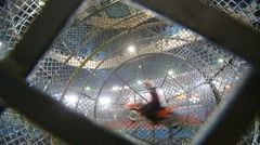 A Biker drives inside the metal mesh ball on entertainment show Stock Footage