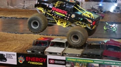 Monster Truck jumping over old cars at sports entertainment show Stock Footage