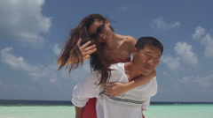 Asian Man Gives His Girlfriend Piggyback Ride On Romantic Island Of Maldives Stock Footage