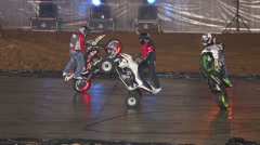 Three stuntman perform a stunt on quad bike and two motorcycles Stock Footage