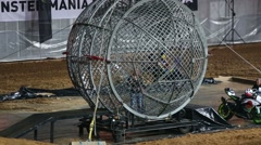 Biker rides around girl in a small circular cage on sports show Stock Footage