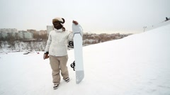 Snowboarder girl with snowboard standing on a hillside Stock Footage
