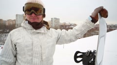 Girl snowboarder stands on the slope and takes off her sunglasses Stock Footage