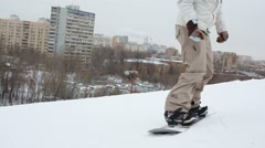 Snowboarder jumping up the hill and slowly descends Stock Footage