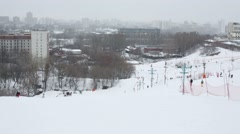 Skiers descend the hill near the city at winter overcast day Stock Footage