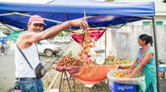 Selling lychees on street in mauritius Stock Footage