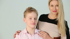 Happy mother and son next to wall, woman hugging boys shoulders Stock Footage