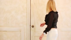 Beautiful blonde girl exits the room and waving goodbye Arkistovideo
