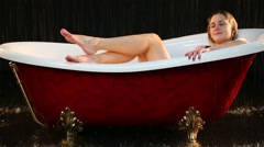 Girl lying with eyes closed in a bathtub under the dripping water Stock Footage