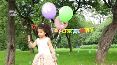 Little girl with three balloons catches soap bubbles Stock Footage