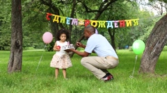 Father presents daughter a cake in her third birthday Stock Footage