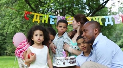 Family celebrates birthday of the daughter in the park - stock footage