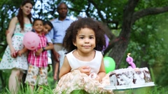 Girl squatting, blow out candle on cake, behind stands family Stock Footage