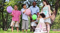 Happy family celebrating a birthday party in the park with cake Stock Footage