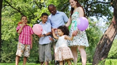 Family celebrating a birthday party in the park, children playing Stock Footage