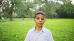 Close-up of boy in the striped shirt comes out of focus in park Stock Footage