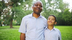 Happy father and son standing embracing in the summer park Stock Footage