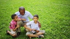 Father sitting on his haunches and hugs his sons on a glade Stock Footage