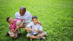 A man sitting on the grass in the summer park with his sons Stock Footage