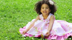 Little girl in pink dress sitting spread out hem of the dress Stock Footage