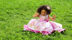 Little girl in pink dress sitting on the grass and waving hands Stock Footage
